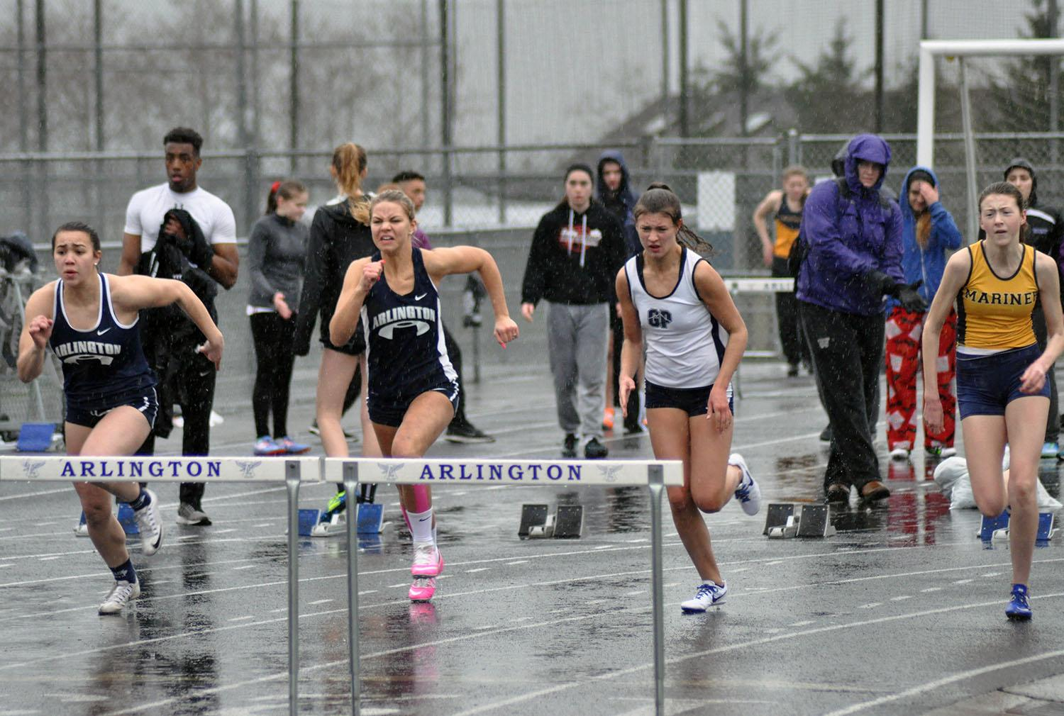Female athletes compete in a hurdles competition.