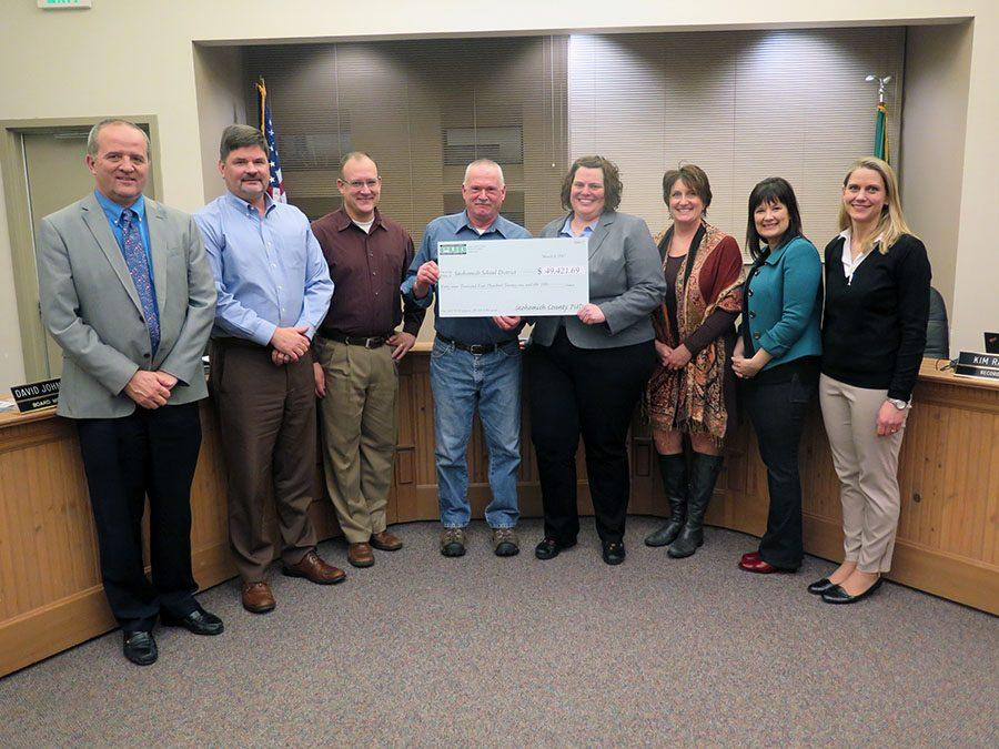 The School Board receiving a check from the PUD.