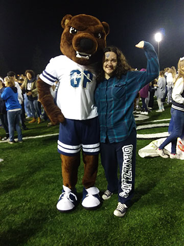 Student poses with the mascot at the homecoming game.