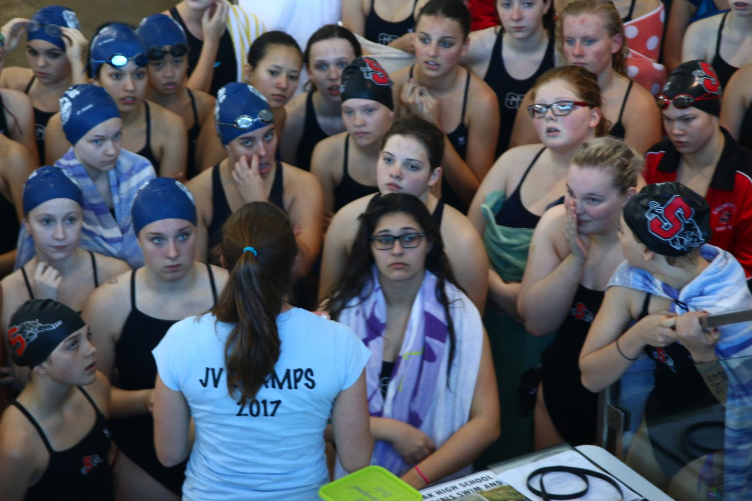Glacier Peak and Snohomish gathering with assistant coach, Jenny Service, before a meet.