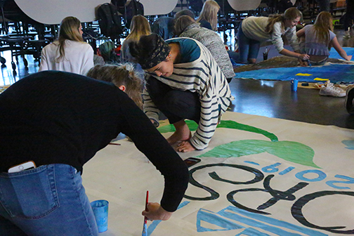 Seniors Hannah Clymer and Charlotte Offin work together to complete the Seniors' Homecoming run-through poster.