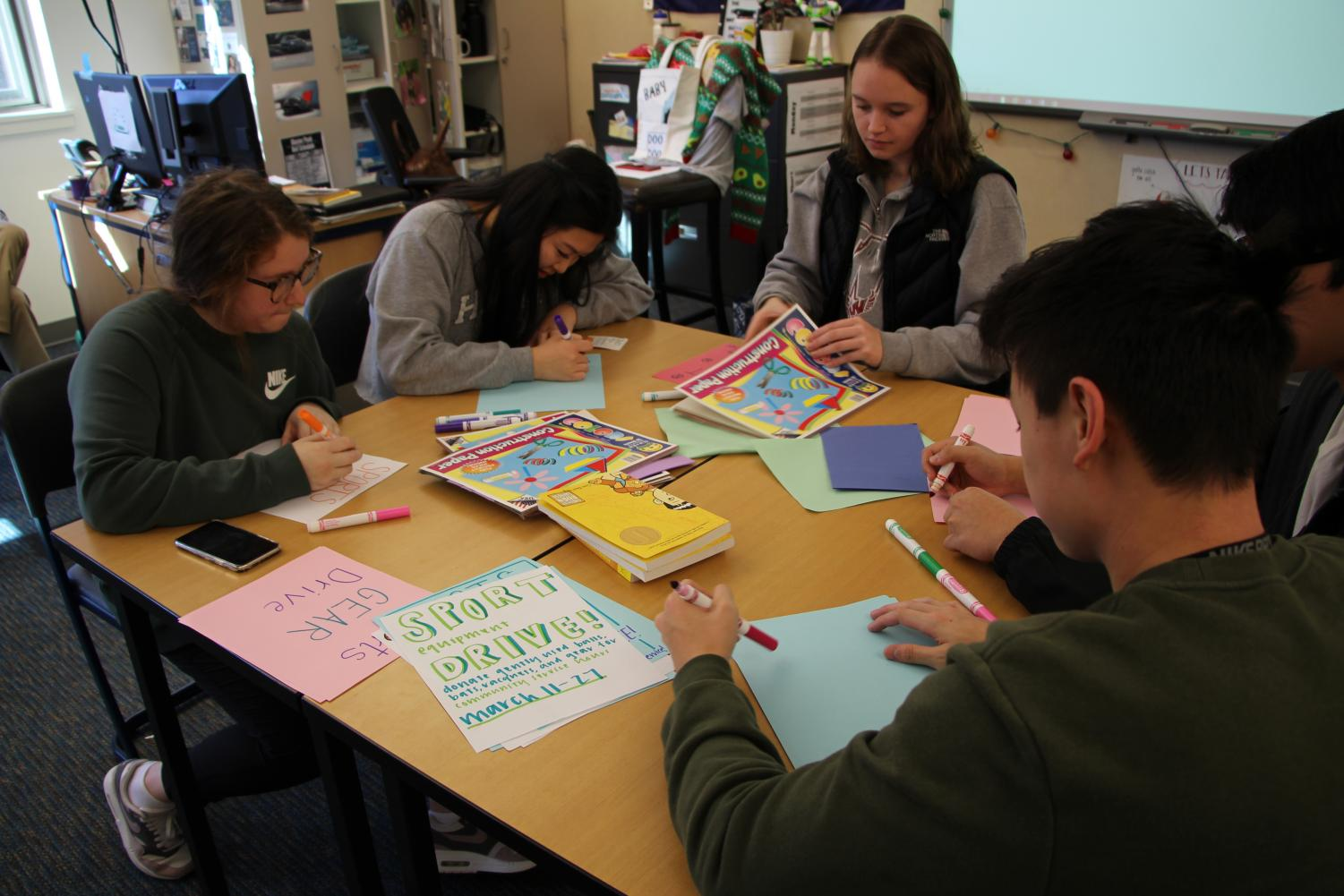 Students working on posters for the Key club sports equipment drive