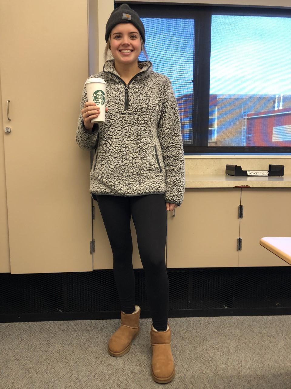 Kaylee wearing the Classic Mini Ugg's, a Carhartt Beanie, drinking a warm oat milk latte.